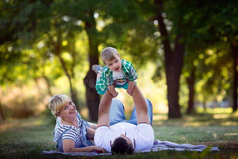 Niño pequeño con sus padres que se acuestan en la hierba foto de archivo