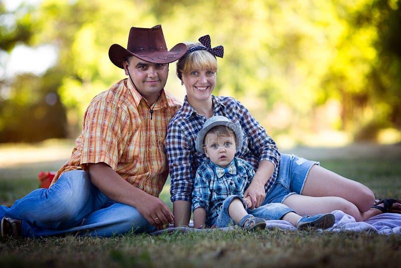 Niño pequeño con sus padres que se acuestan en la hierba imagen de archivo libre de regalías