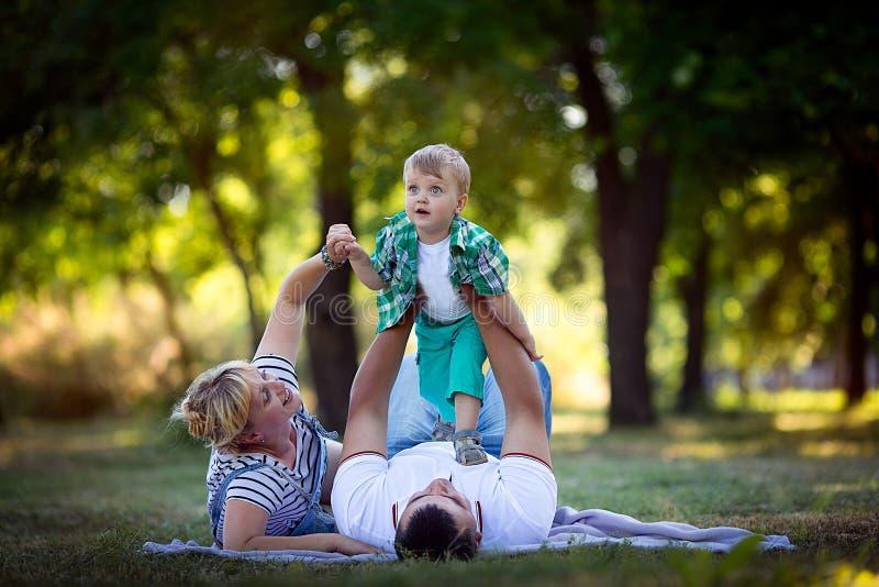 Niño pequeño con sus padres que se acuestan en la hierba fotos de archivo libres de regalías