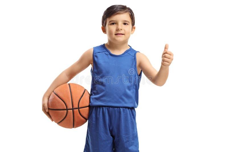 Niño pequeño con un baloncesto que hace un pulgar encima del gesto imágenes de archivo libres de regalías