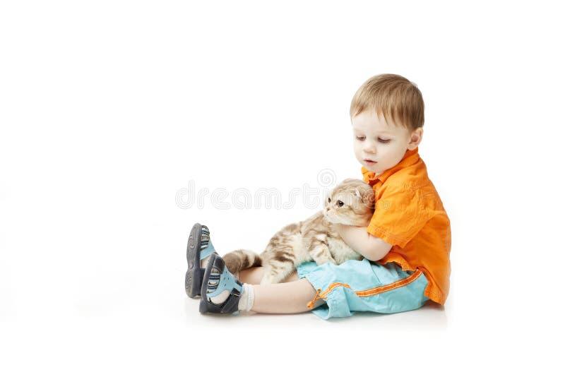 Niño pequeño con un gato en un fondo blanco imagen de archivo