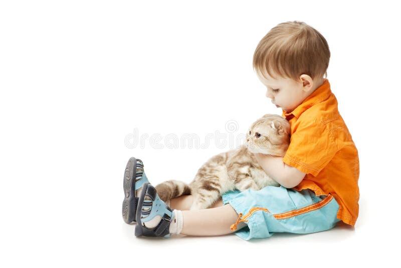 Niño pequeño con un gato en un fondo blanco fotografía de archivo libre de regalías