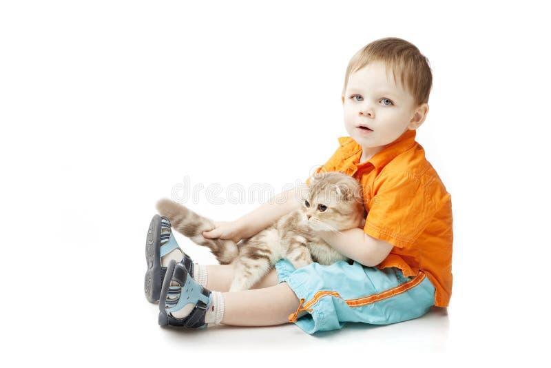Niño pequeño con un gato en un fondo blanco foto de archivo