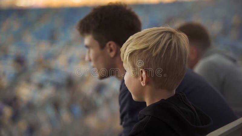 Niño pequeño con un más viejo hermano en el estadio de fútbol, la educación y la fraternidad foto de archivo libre de regalías
