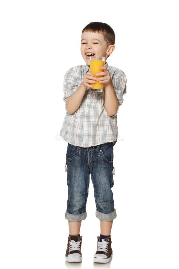 Niño pequeño con un vidrio de risas del jugo. fotos de archivo libres de regalías