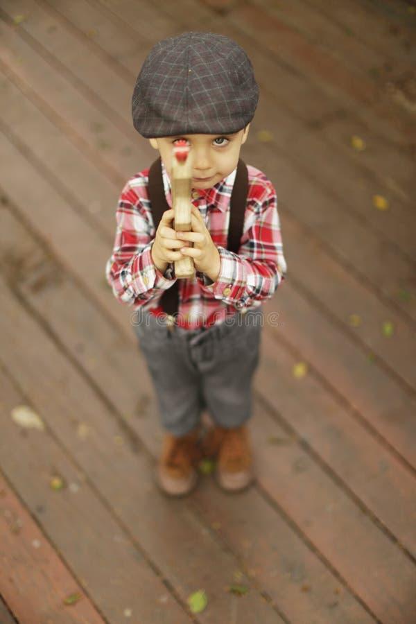 Niño pequeño con una cara seria que señala un arma de madera del juguete en la cámara imagen de archivo