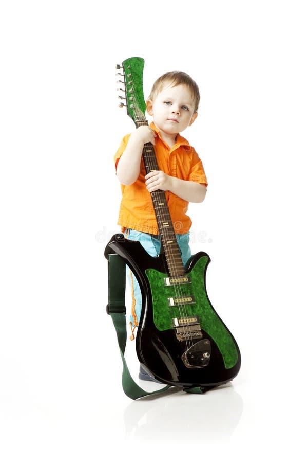 Niño pequeño con una guitarra en un fondo blanco foto de archivo libre de regalías