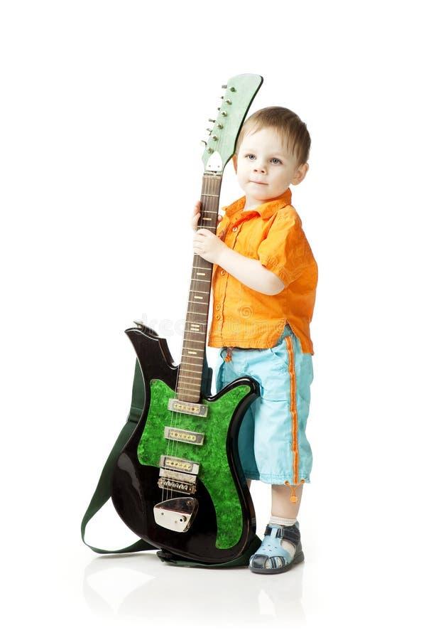 Niño pequeño con una guitarra en un fondo blanco imagen de archivo