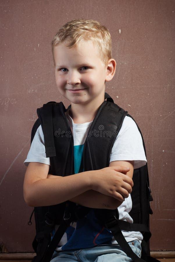 Niño pequeño con una mochila negra grande, individuo con el pelo rubio que presenta en una pizarra, foto de archivo libre de regalías