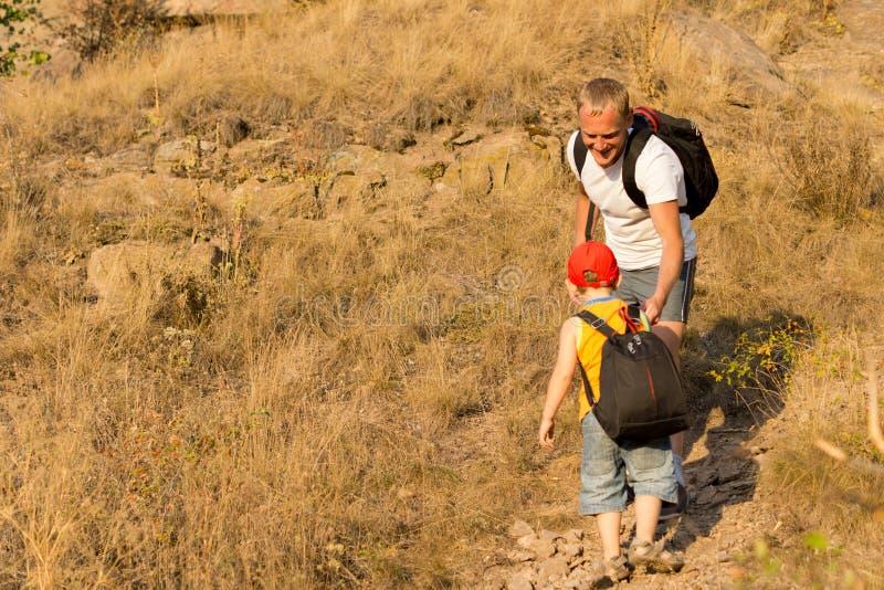 Niño pequeño con una mochila que sube una montaña fotos de archivo