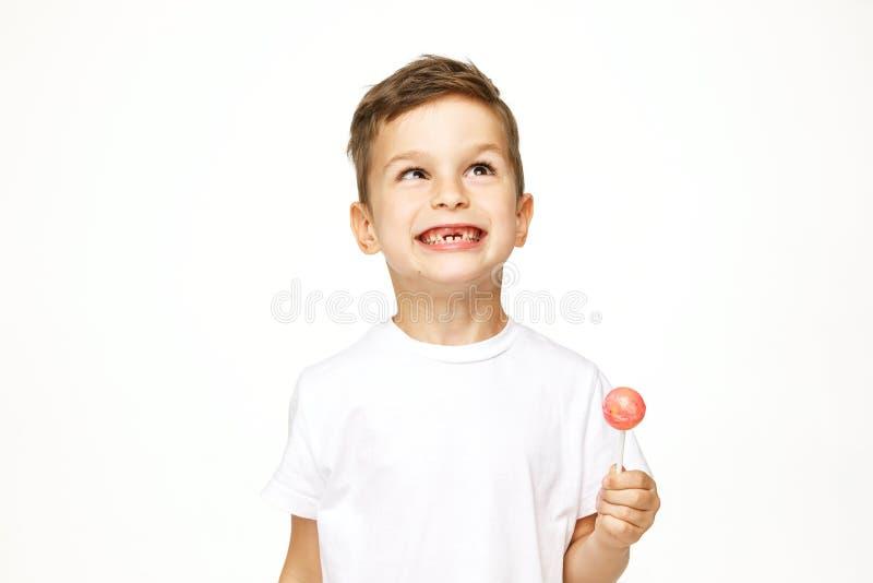 Niño pequeño con una piruleta en un fondo blanco imagenes de archivo
