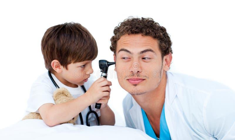 Niño pequeño concentrado que juega con el doctor imágenes de archivo libres de regalías