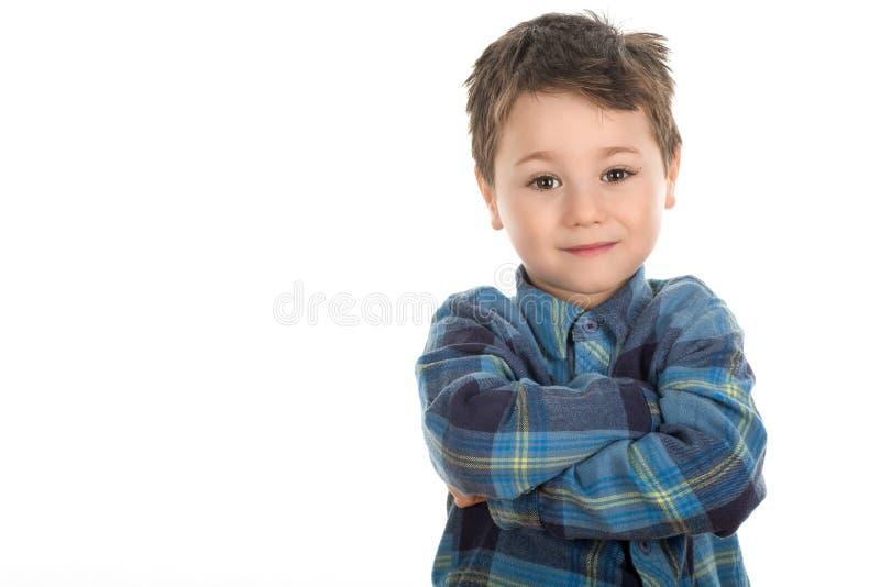 Niño pequeño confiado con las manos cruzadas foto de archivo