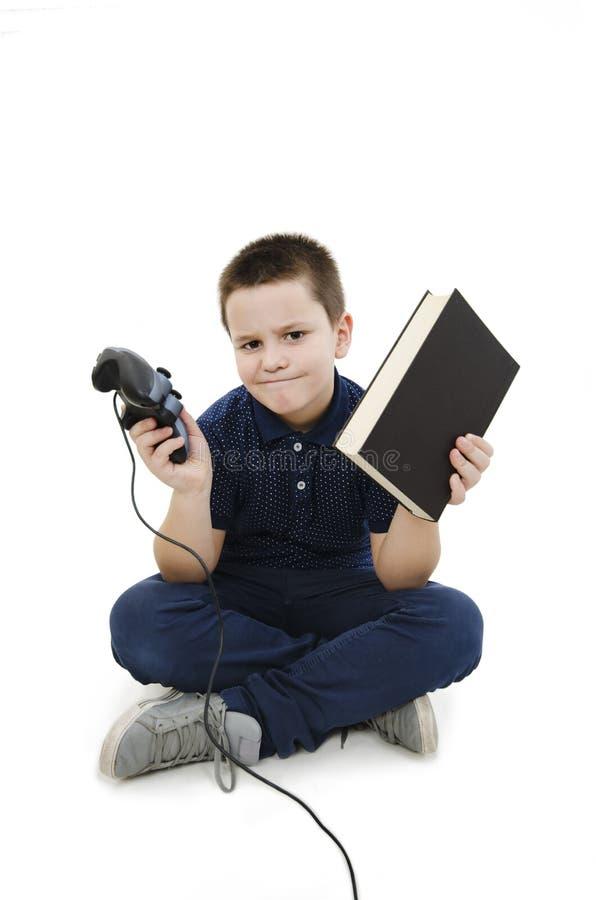 Niño pequeño confuso que sostiene un libro y un regulador del videojuego imagenes de archivo