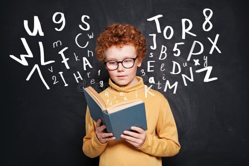 Niño pequeño curioso en vidrios que lee un libro contra la pizarra imagen de archivo libre de regalías