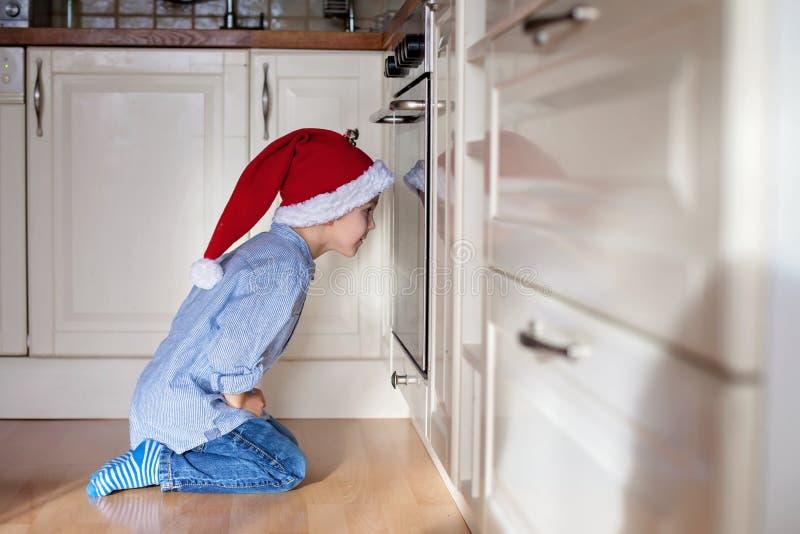 Niño pequeño curioso, jengibre de observación empanar las galletas en el horno fotografía de archivo