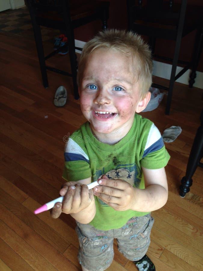 Niño pequeño dañoso hecho frente sucio fotografía de archivo