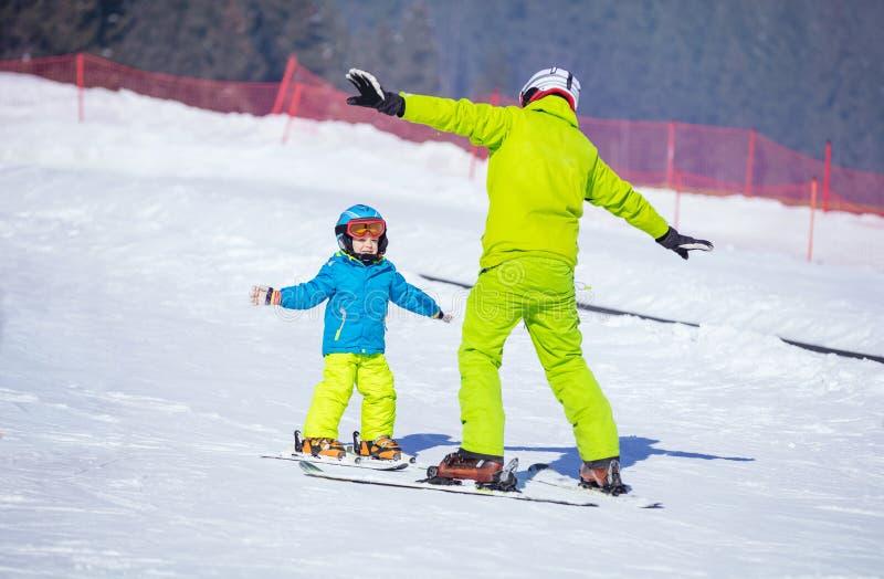 Niño pequeño de enseñanza del instructor a esquiar imagenes de archivo