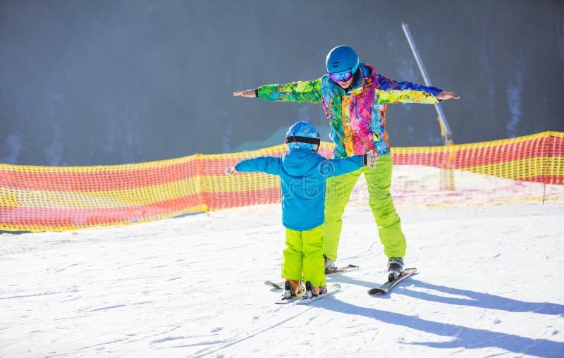 Niño pequeño de enseñanza del padre o del instructor a esquiar imagenes de archivo