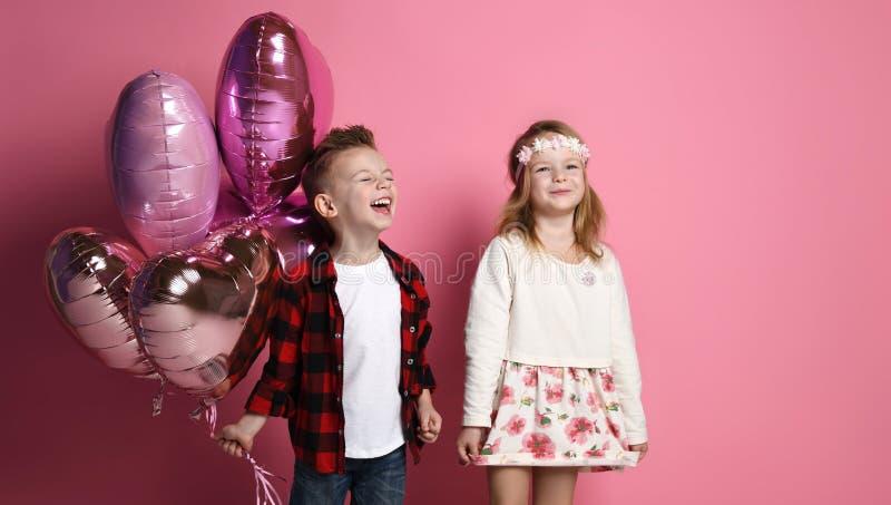 Niño pequeño de Laughting y niños sonrientes felices de la niña con los globos del corazón del color en colores pastel para día d imagen de archivo libre de regalías