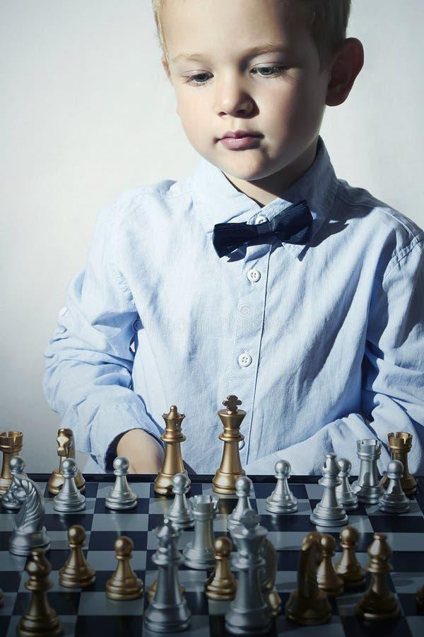 Niño pequeño de moda que juega a ajedrez Pequeño niño del genio Juego inteligente Tablero de ajedrez fotos de archivo libres de regalías