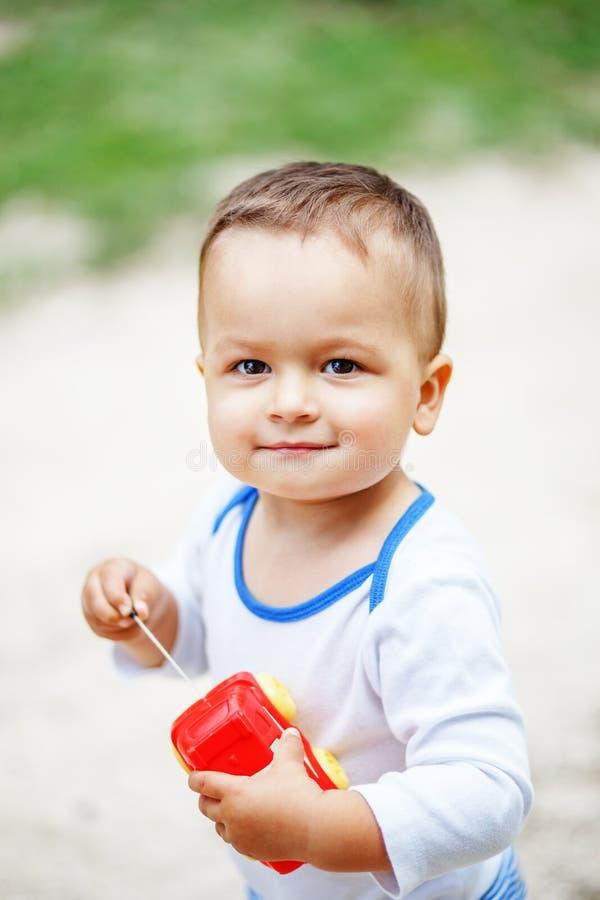 Niño pequeño de ojos marrones lindo que juega con un coche plástico rojo del juguete imagen de archivo