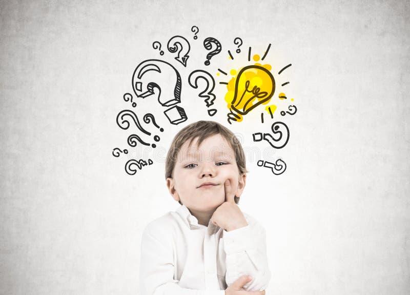 Niño pequeño de pensamiento, signos de interrogación, idea foto de archivo