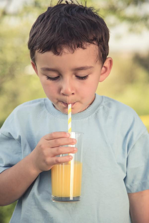 Niño pequeño del niño del niño que bebe el vintage al aire libre de la bebida del zumo de naranja foto de archivo