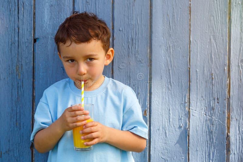 Niño pequeño del niño del niño que bebe la copia del copyspace de la bebida del zumo de naranja imagen de archivo