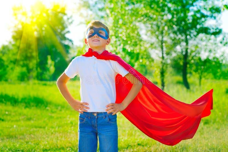 Niño pequeño del super héroe sobre fondo de la naturaleza fotografía de archivo libre de regalías