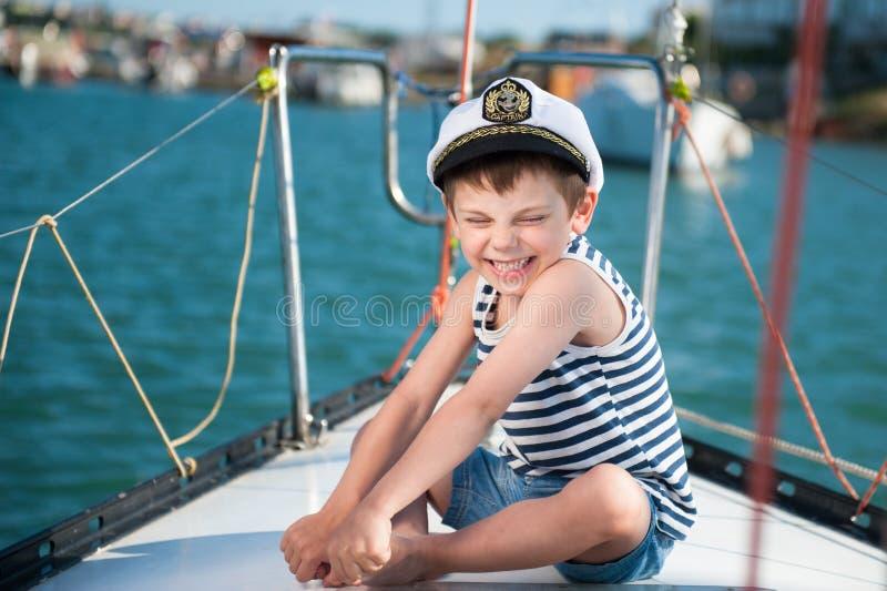 Niño pequeño delicioso feliz lindo en sombrero del capitán en tablero del yate en travesía del verano imagen de archivo libre de regalías