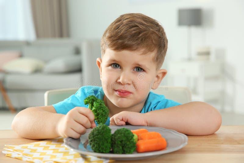 Niño pequeño descontentado que come verduras en la tabla imagen de archivo