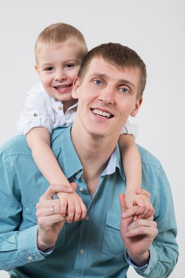 Niño pequeño detrás de abrazos felices del padre imagen de archivo