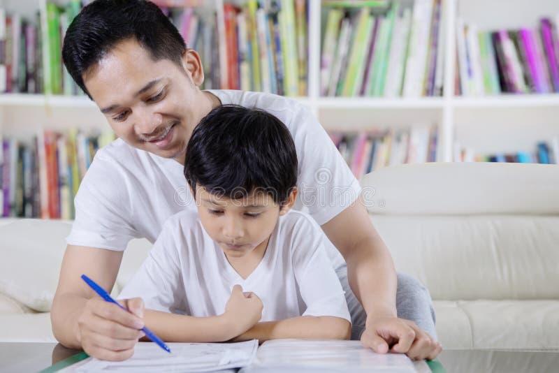 Niño pequeño dirigido por su padre para leer un libro foto de archivo