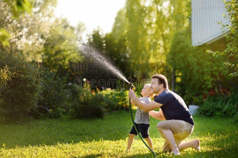 Niño pequeño divertido con su padre que juega con la manguera de jardín en patio trasero soleado fotos de archivo libres de regalías