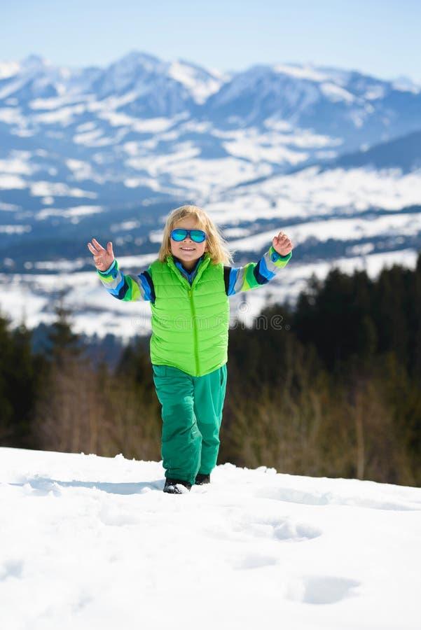 Niño pequeño divertido en gafas de sol en montañas del invierno en una d soleada fotografía de archivo