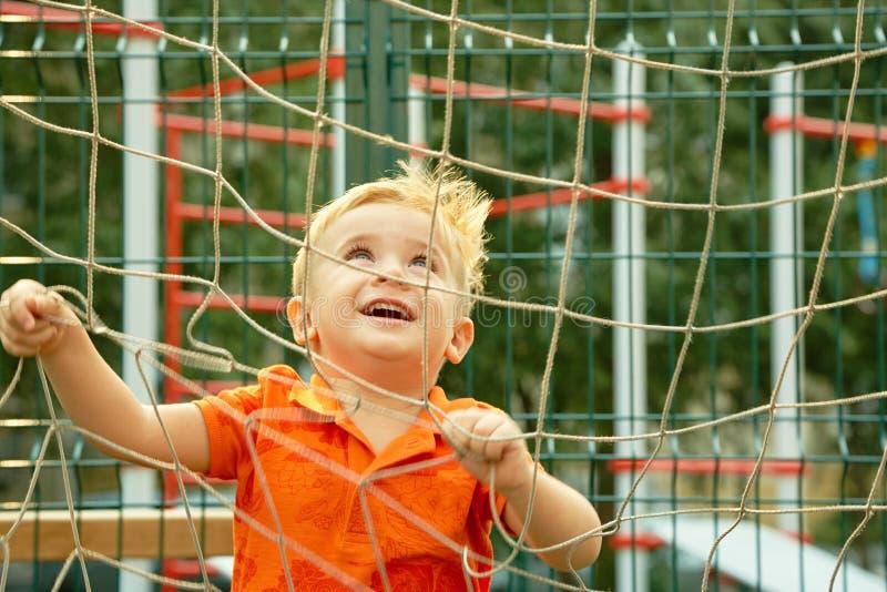 Niño pequeño divertido en patio con la rejilla de la puerta del fútbol jugar al niño en la tierra de deportes imágenes de archivo libres de regalías