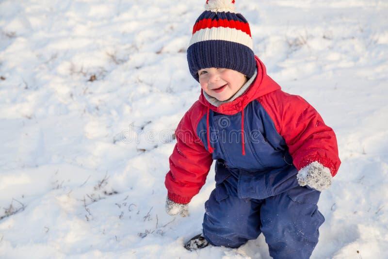 Niño pequeño divertido que camina en nieve foto de archivo libre de regalías