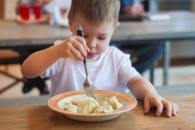 Niño pequeño divertido que come en un café, concepto de la comida imagen de archivo libre de regalías