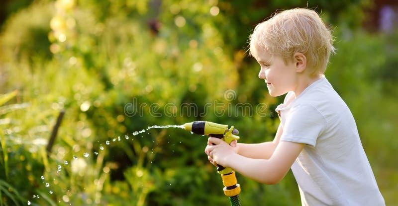 Niño pequeño divertido que juega con la manguera de jardín en patio trasero soleado imágenes de archivo libres de regalías
