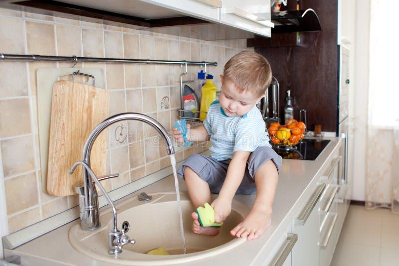 Niño pequeño divertido que se sienta en el vector de cocina foto de archivo libre de regalías