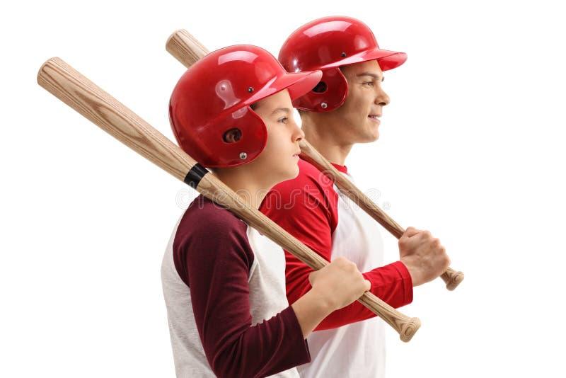 Niño pequeño e individuo con los bates de béisbol y los cascos fotografía de archivo