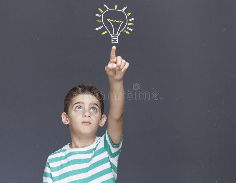 Niño pequeño elegante que tiene una idea imagen de archivo libre de regalías
