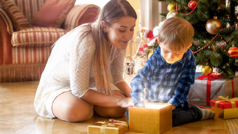 Niño pequeño emocionado alegre que saca el regalo de la Navidad de la caja de regalo mágica que brilla intensamente fotografía de archivo libre de regalías