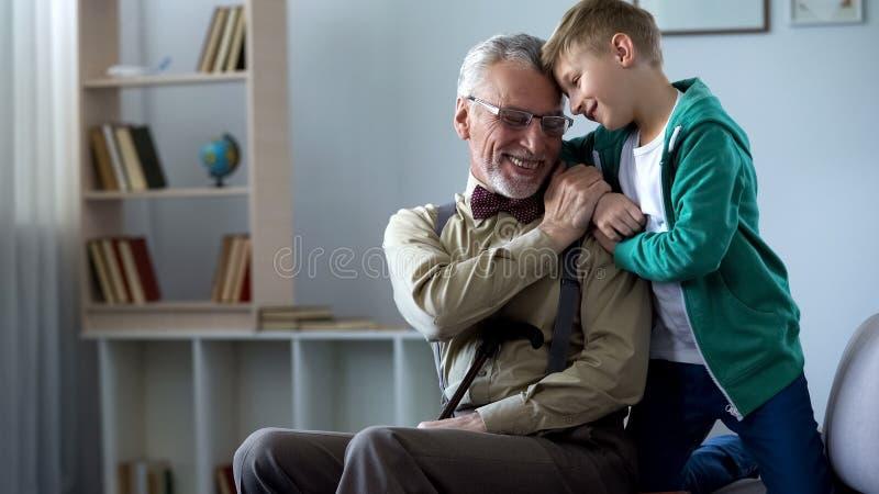 Niño pequeño emracing el viejo hombre, extremadamente feliz de visitar al abuelo los fines de semana fotografía de archivo