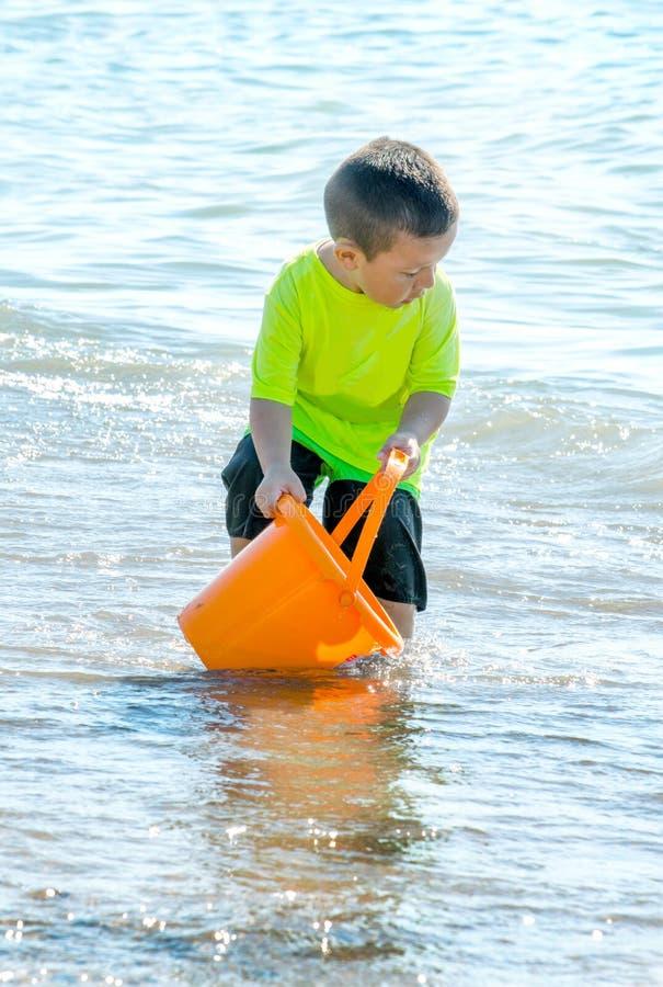 Niño pequeño en agua con el cubo anaranjado imagen de archivo libre de regalías