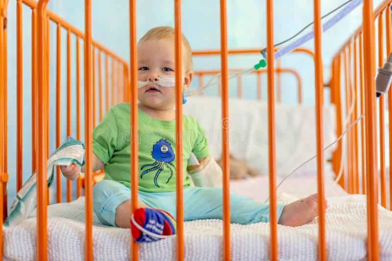 Niño pequeño en cama de hospital fotografía de archivo