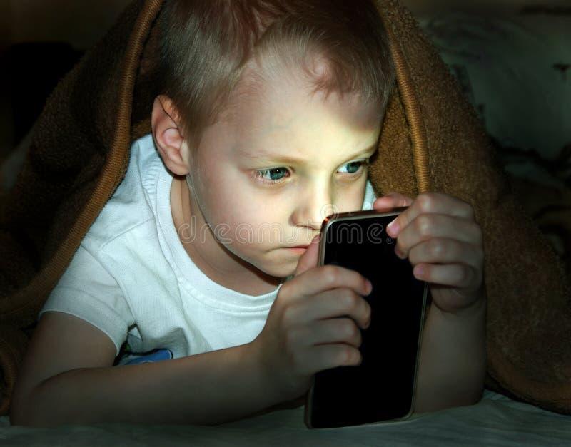 Niño pequeño en cama debajo de una manta que mira el smartphone la noche foto de archivo libre de regalías