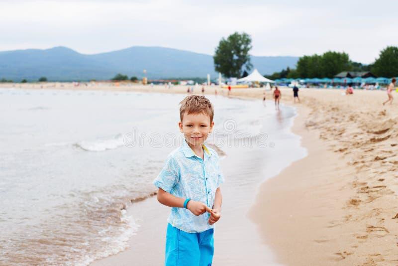 Niño pequeño en camisa y pantalones cortos en la arena de la playa Hav del niño pequeño fotos de archivo