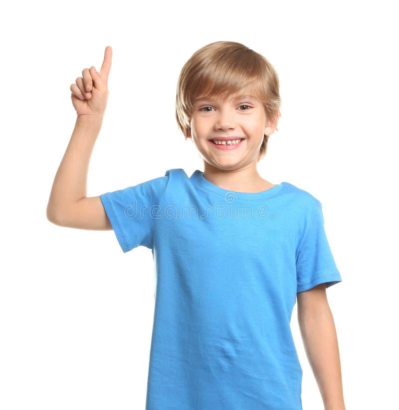 Niño pequeño en camiseta y con el dedo índice aumentado en el fondo blanco imagenes de archivo